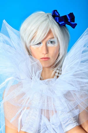 Portrait of an extravagant blonde model over blue background.  photo