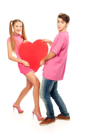 Funny young love couple posing together with red heart. Isolated over white background. photo