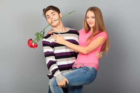 flirting women: Happy young love couple posing together with red rose.