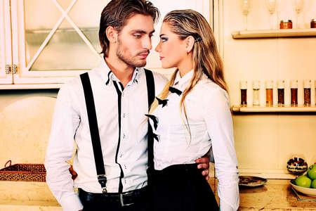 jovenes enamorados: Retrato de un hombre guapo de moda con encanto de mujer posando en el interior.
