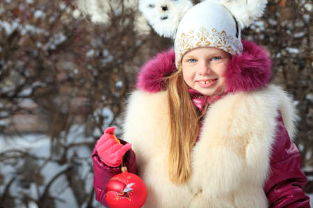 Cute girl in Santa Claus cap at a winter park. Christmas.  photo