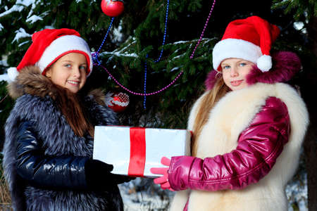 Two girls in Santa Claus cap celebrating Christmas at a winter park.  photo