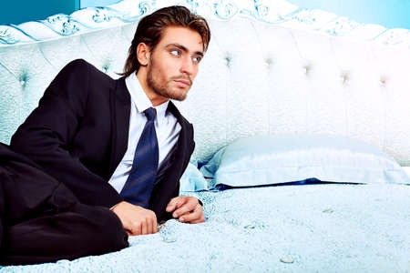 bed clothes: Portrait of a handsome fashionable man posing in the interior. Stock Photo