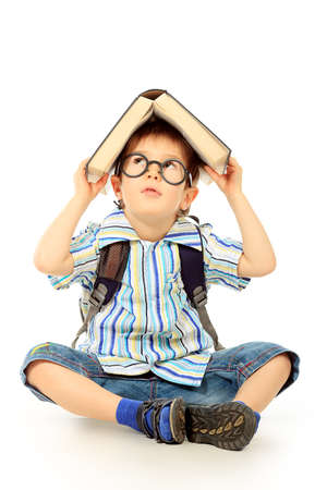 Portrait of a little boy in spectacles reading a book. Isolated over white background. Stock Photo - 12268226