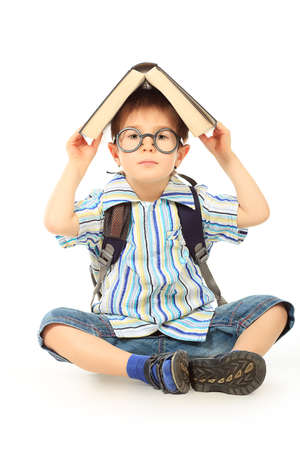 funny glasses: Portrait of a little boy in spectacles reading a book. Isolated over white background.