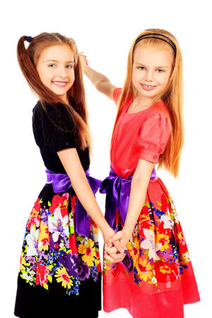Portrait of two little girls sisters posing at studio. Isolated over white. Stock Photo - 12308987