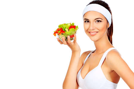 Portrait of a beautiful young woman eating vegetable salad. Isolated over white background. Stock Photo - 12309054
