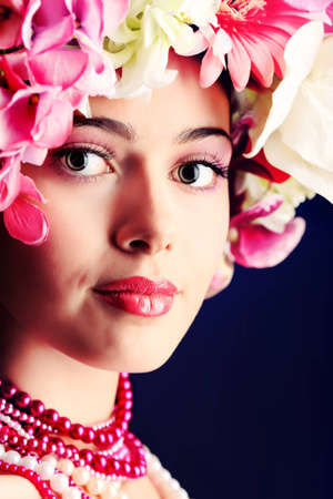 Portrait of a beautiful spring girl wearing flowers hat. Studio shot. Stock Photo - 12309097