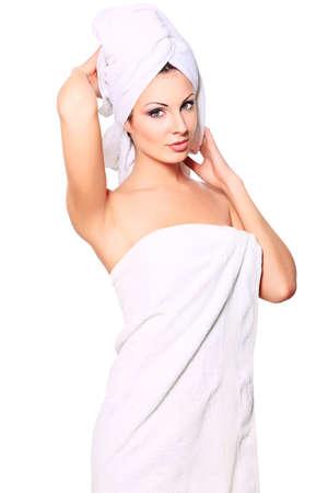 Belle jeune femme posant dans une serviette blanche. Spa, soins de santé. Isolé sur blanc.
