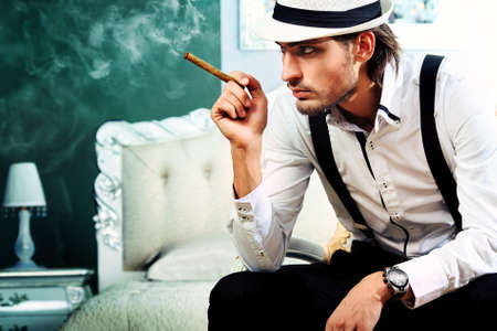 smoking cigar: Portrait of a handsome fashionable man posing in the interior. Stock Photo