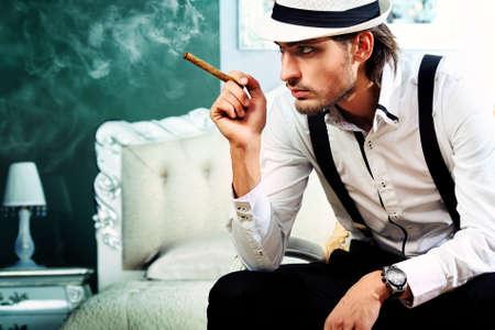 cigar smoking man: Retrato de un hombre guapo de moda posando en el interior.