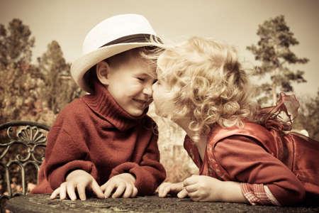 romantic kiss: Romantic children at a park. Retro style.