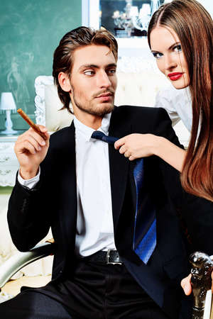 rich couple: Portrait of a handsome fashionable man with  charming woman posing in the interior. Stock Photo