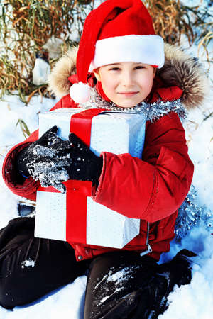 Happy boy sitting with  present outdoor on winter.  photo