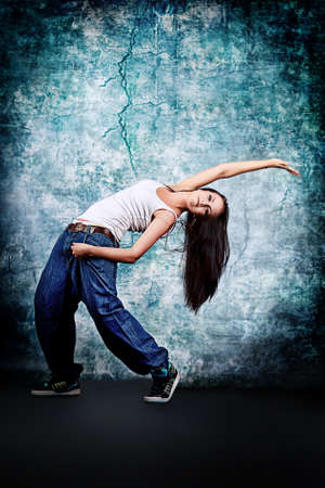 Modern teenage girl dancing hip-hop at studio. photo