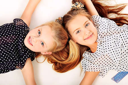schoolchild: Portrait of two little girls sisters posing at studio. Isolated over white.