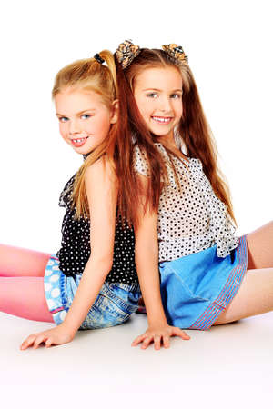 Portrait of two little girls sisters posing at studio. Isolated over white. Stock Photo - 12351393