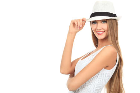 girl in a hat: Beautiful young woman in light summer dress posing  over white. Stock Photo