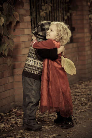 romantic hug: Cute children hugging each other at a park. Retro style.