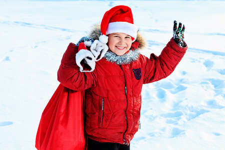 Happy boy standing with Christmas sack of presents outdoor.  Stock Photo - 12351572