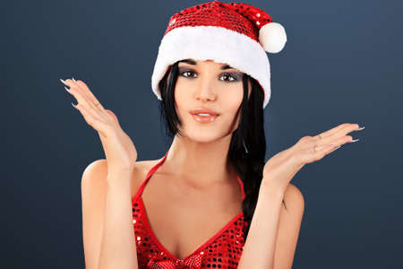 Beautiful young woman in Santa Claus clothes over grey background. photo