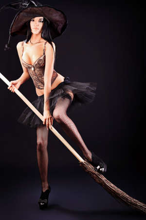 Charming halloween witch with broom over black background. photo