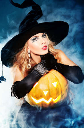 Charming halloween witch over black background. photo