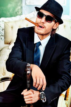 hombre fumando puro: Retrato de un hombre guapo de moda posando en el interior.