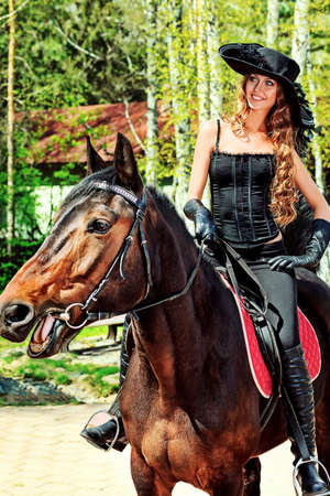 historical events: Beautiful young woman in medieval costume is riding on horseback. Stock Photo