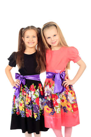 Portrait of two little girls sisters posing at studio. Isolated over white. Stock Photo - 12521687
