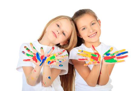 enfants qui rient: Portrait de deux jolies filles en appr�ciant la peinture. Education. Isol� sur fond blanc.