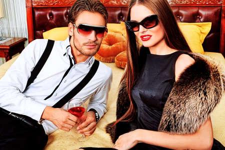 金持ち: 内部でポーズをとって魅力的な女性とハンサムなファッショナブルな男の肖像画。