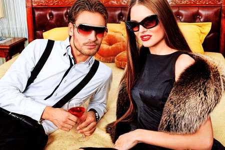 rich people: Portrait of a handsome fashionable man with  charming woman posing in the interior. Stock Photo