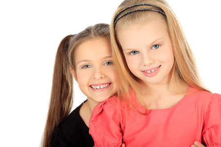 schoolgirls: Portrait of two little girls sisters posing at studio. Isolated over white.