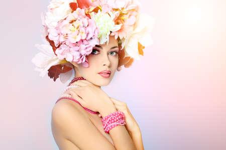Portrait of a beautiful spring girl wearing flowers hat. Studio shot. photo