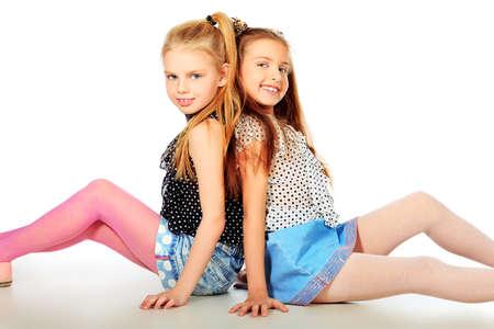 entre filles: Portrait de deux s?urs petites filles posant dans le studio. Isol� sur blanc. Banque d'images