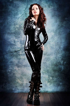 Fashion shot of a woman in black glossy overall and platform boots. photo