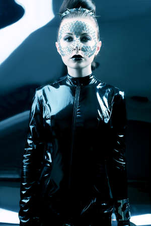 Conceptual shot of a woman in black glossy overall and metal buttons on her face. Stock Photo - 12521758