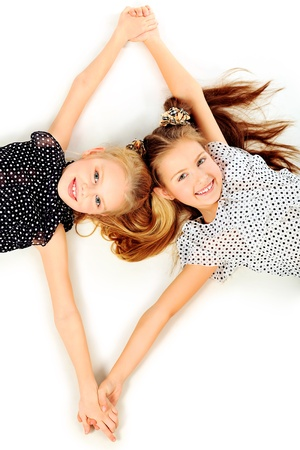 Portrait of two little girls sisters posing at studio. Isolated over white. photo