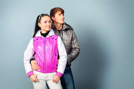 Couple of fashion models in winter, spring clothes posing at the studio. photo