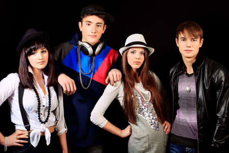 Group of stylish young people posing over black background.  photo