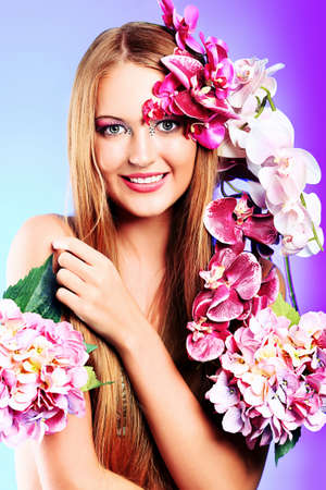 Portrait of a beautiful tanned woman posing with flowers. photo