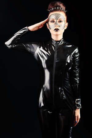 female soldier: Conceptual shot of a woman in black glossy overall and metal buttons on her face.