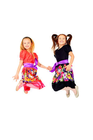 Portrait of two happy girls sisters jumping at studio. Isolated over white. Stock Photo - 12613033