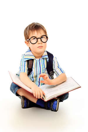 Portrait of a little boy in spectacles reading a book. Isolated over white background. Stock Photo - 12613338