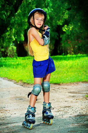 Little girl in roller skates at a park. photo
