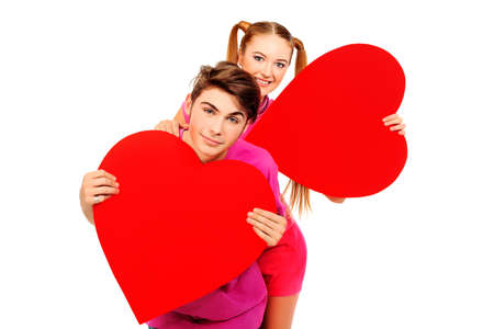 Happy young love couple posing together with red hearts. Isolated over white background. photo