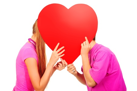 Happy young love couple kissing behind red heart. Isolated over white background. photo