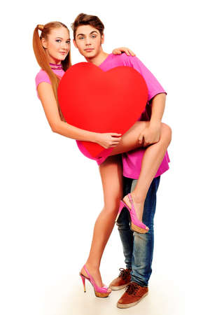 Happy young love couple posing together with red heart. Isolated over white background. photo