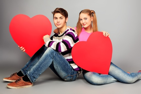 flirting women: Happy young love couple posing together with red hearts.  Stock Photo